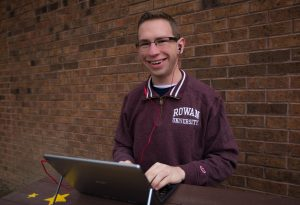 Kevin at Rowan University outside with his headbuds and iPad