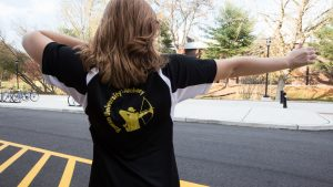 Rowan student Melissa in archery shirt holding position of bow and arrow outside of Westby