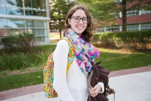 Rowan student Chrissie outside on campus holding her bag and jacket