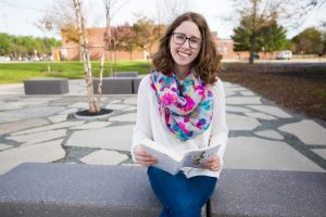 Rowan student Chrissie reading a book outside Robinson Hall at Rowan University