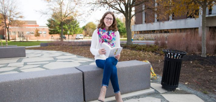Rowan student Chrissie outside of Robinson Hall reading a book