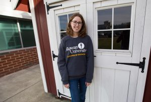 Rowan student Chrissie wearing College of Education sweatshirt outside of James Hall on campus