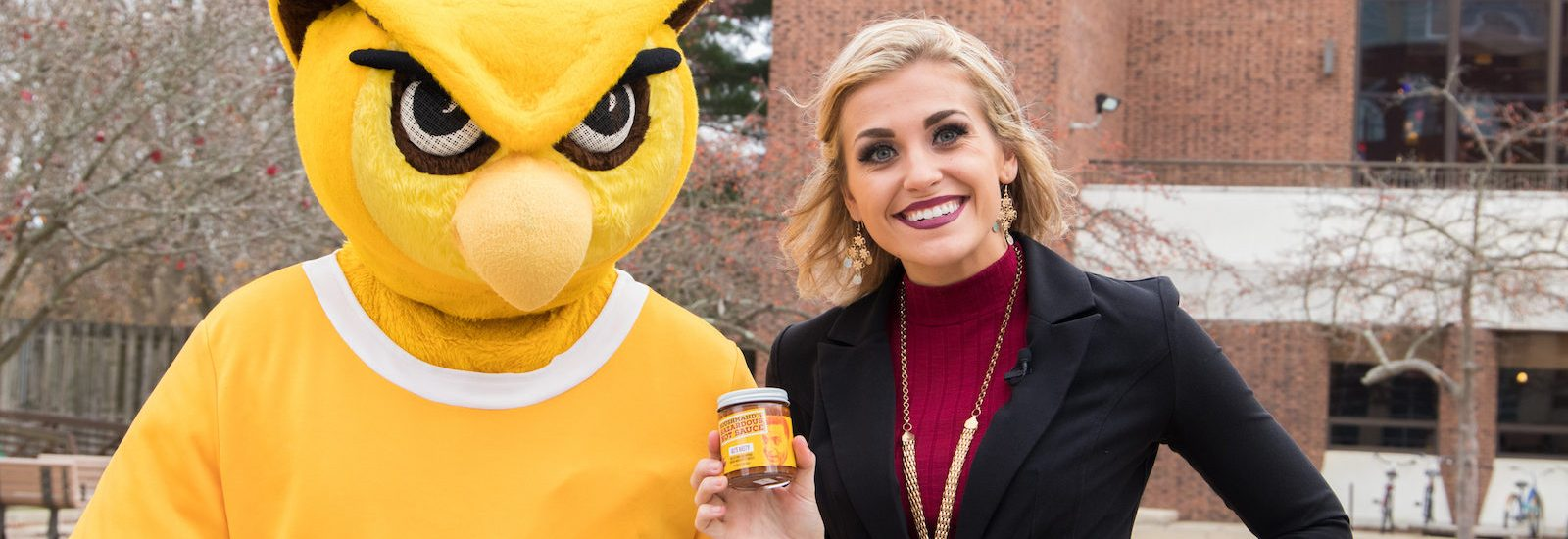 Rowan student stands next to the prof holding hot sauce
