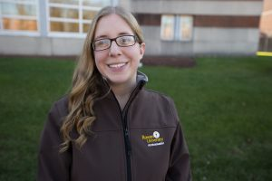 Rowan student pictured in her admissions ambassador jacket outside