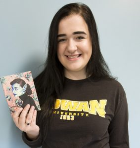 Rowan writing arts major Kaitlyn holding the Avant Literary Magazine at Rowan University