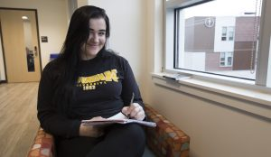 Kaitlyn, writing arts major at Rowan University, sitting writing in book in Victoria St. building next to High St. building