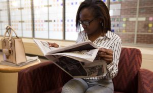 Rowan student Destiny reading newspaper The Whit inside James Hall