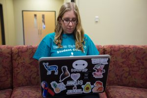 Rowan student typing on her laptop on Rowan campus inside James Hall