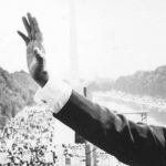 iconic photo of Dr. Martin Luther King waving at crowd after a speech