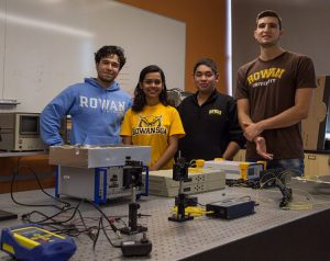 four students stand behind equipment in a Rowan University engineering lab