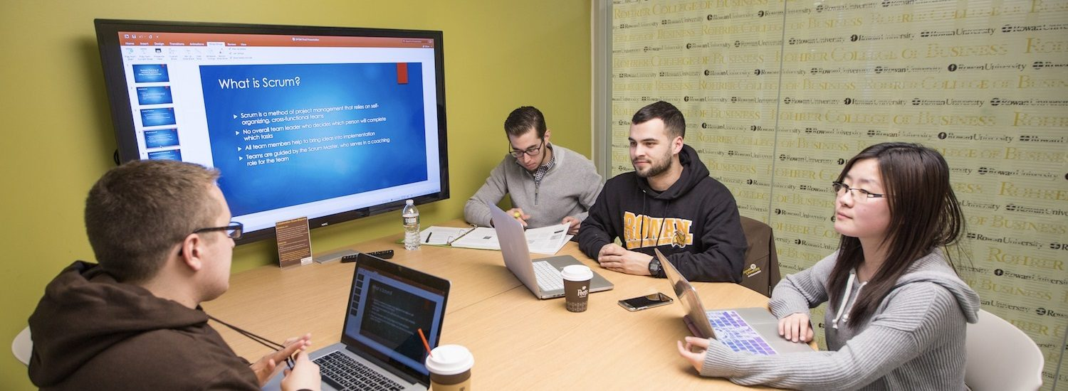 Carlo sits at a collaboration room in Business Hall with other students