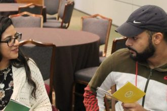 Two students sit at a table speaking to each other about the event.