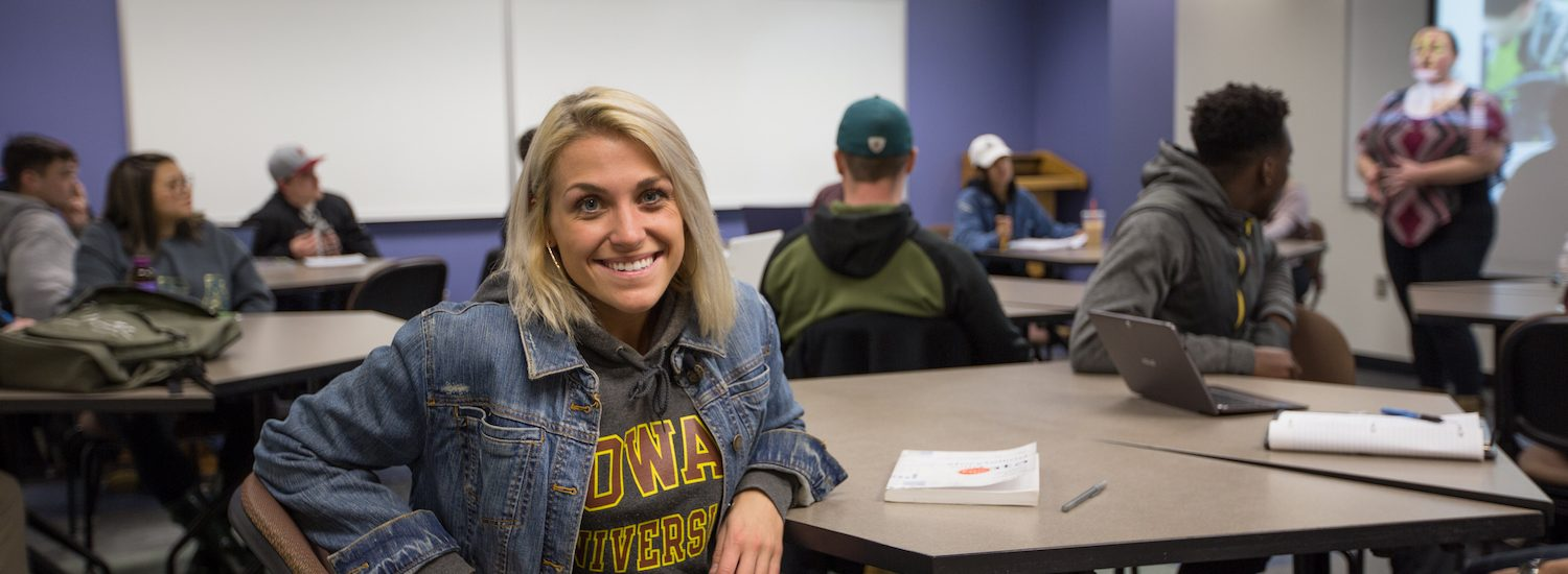 vanessa sitting in a college of communication and creative arts classroom