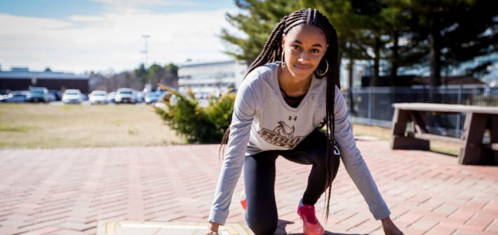 Sidney in track pose outside the track field at Rowan