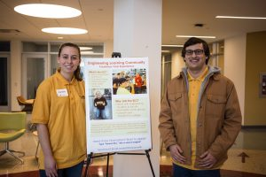 Two representatives from the Engineering Learning Community stand in front of their poster.
