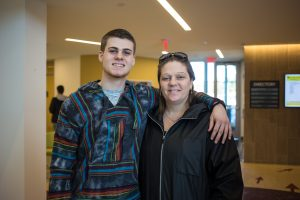 A student and his mom stand in Engineering Hall smiling for a photo.
