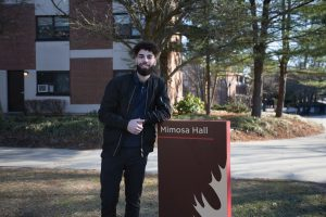 Nabil standing outside of Mimosa Hall, smiling.