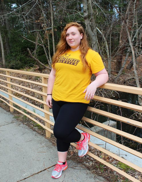 Olivia leans on a bridge at Rowan University