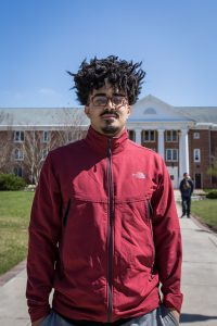 Rowan University student wears red jacket while standing in a portrait pose in front of Chestnut