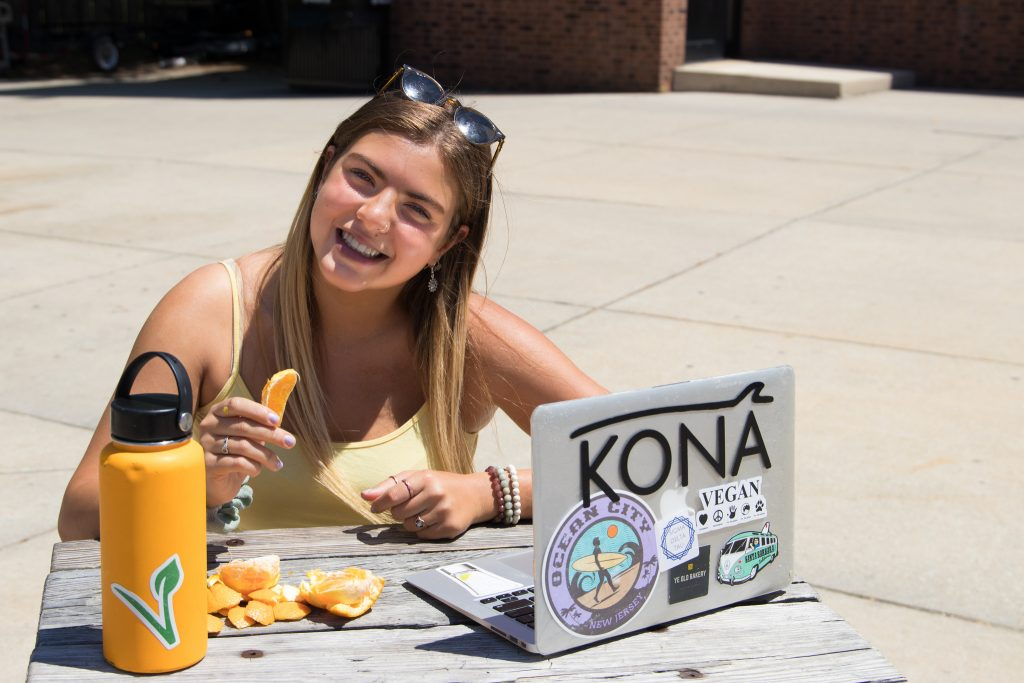 rowan university student outside the student center sitting at a table