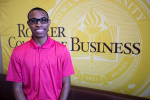 Davon pictured in front of the Rohrer College of Business sign inside the building