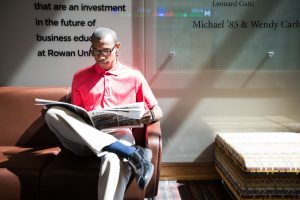 Davon reading the Whit inside the Rohrer COllege of Business building at Rowan University