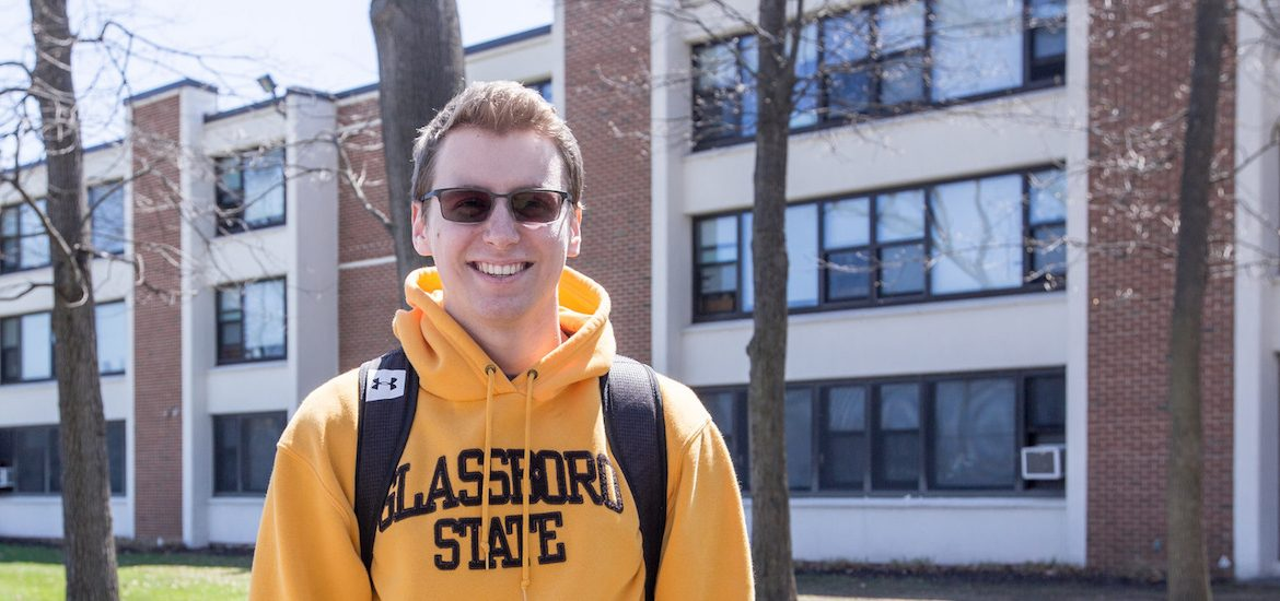 Scott Timko is a resident assistant in Mullica Hall, wearing a yellow sweatshirt that says Glassboro State
