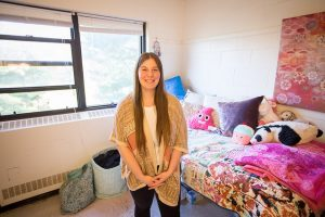 Mimosa resident assistant stands in her bedroom at Rowan University