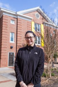 Student wears NorthFace fleece in front of Willow Hall at Rowan University