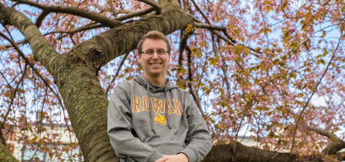 Scott the RA in a pink tree outside Mullica at Rowan