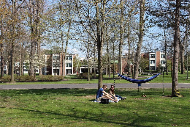 two students sitting near a hammock outside of dorms at rowan university