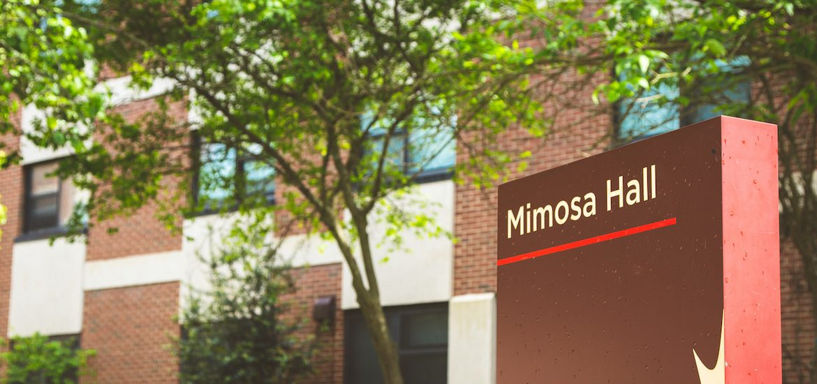 brown sign for Mimosa Hall, in front of building with blooming green trees