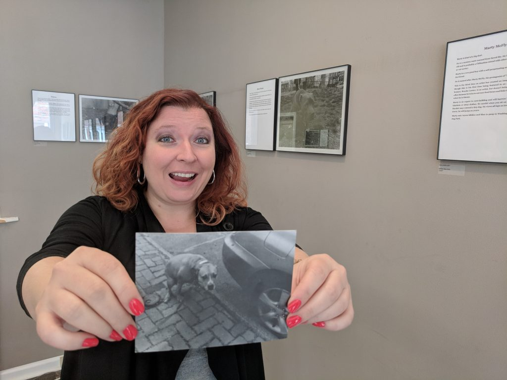Gallery owner Beth stands arms outstretched holding a postcard of one of her pooping dog photographs