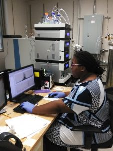 Alana sits at the desk in her research laboratory and examines a chart with data she collected from samples.