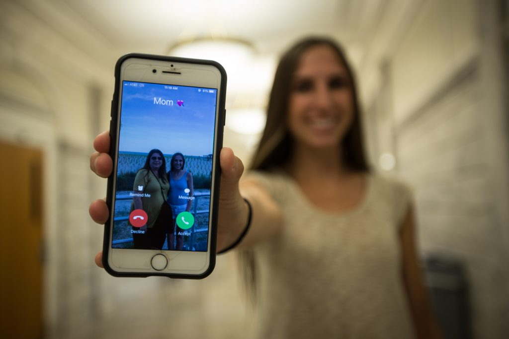 A rowan student holds an iphone calling her mom