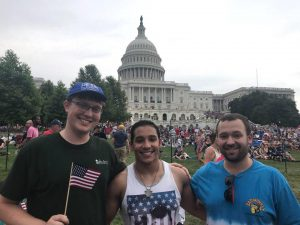Connor and two friends stand at a concert in front of the Capitol building