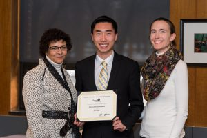 Tyler stands between two Rowan faculty members as he receives his Senior of Distinction Award.