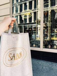 Nicole holds a Sabon bag in front of their NYC store for her Rowan University internship