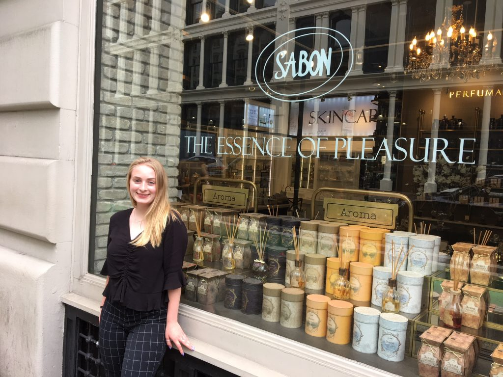 Rowan University's Nicole stands in front of the window front at her Sabon internship in NYC
