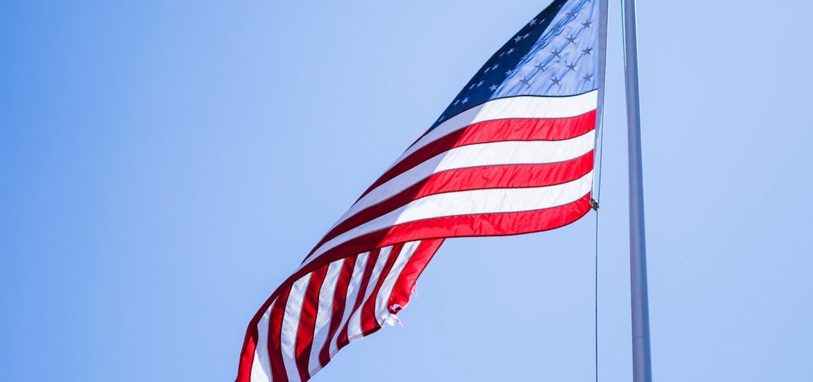American flag waving in sunshine with blue sky in background