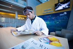 student in lab coat inside science all reading the newspaper