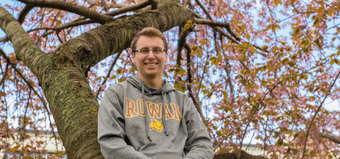 Rowan Alum Scott Timko in a tree with pink flowers