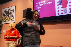 Dr. Monroe hugs a student in the front of the room as she receives a giftcard as a raffle prize.