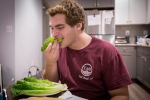 rowan student eating a lettuce wrap inside apartment on campus