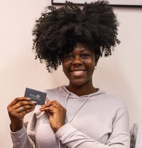 A happy student holds up a Rowan business card holder she received at the event and smiles.