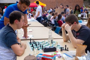 Three boys gather around a table to watch a chess game during the organization fair.