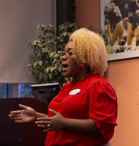 A representative from Target stands before the students, explaining her experience networking.