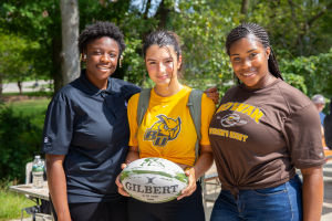 three girls stand together holding a rugby ball, representing their team at the organization fair.