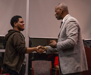 A student shakes faculty member Ruben Britt's hand as part of a demonstration on job interview etiquette.
