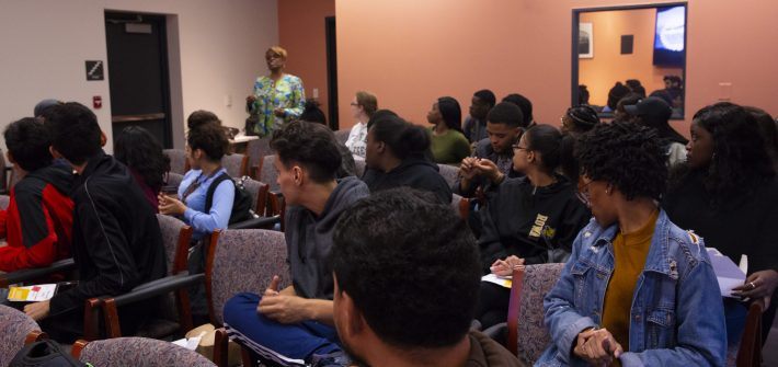 a room full of students looks on as a faculty speaker presents her thoughts on professional behavior at job interviews.